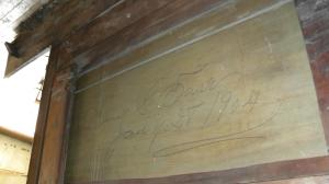 Signed and dated 1904 in beautiful cursive -- likely when the panel was put back in to cover the earlier hole made when a stove was installed