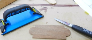 Clean up the curves with the Sloyd knife, then break the edges with the sanding block.