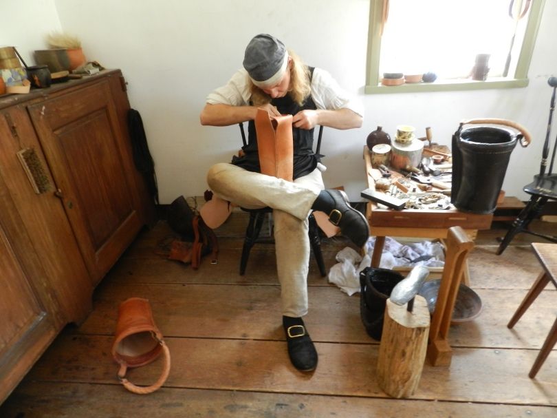 The shoemaker plying his craft -- in this case making a leather bucket.