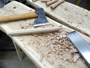 Using the hewing bench, carpenter's axe and timber framing chisel to taper the ends of each pin