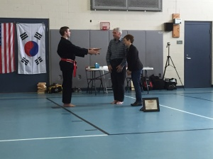 Lee presenting his black belt to his parents